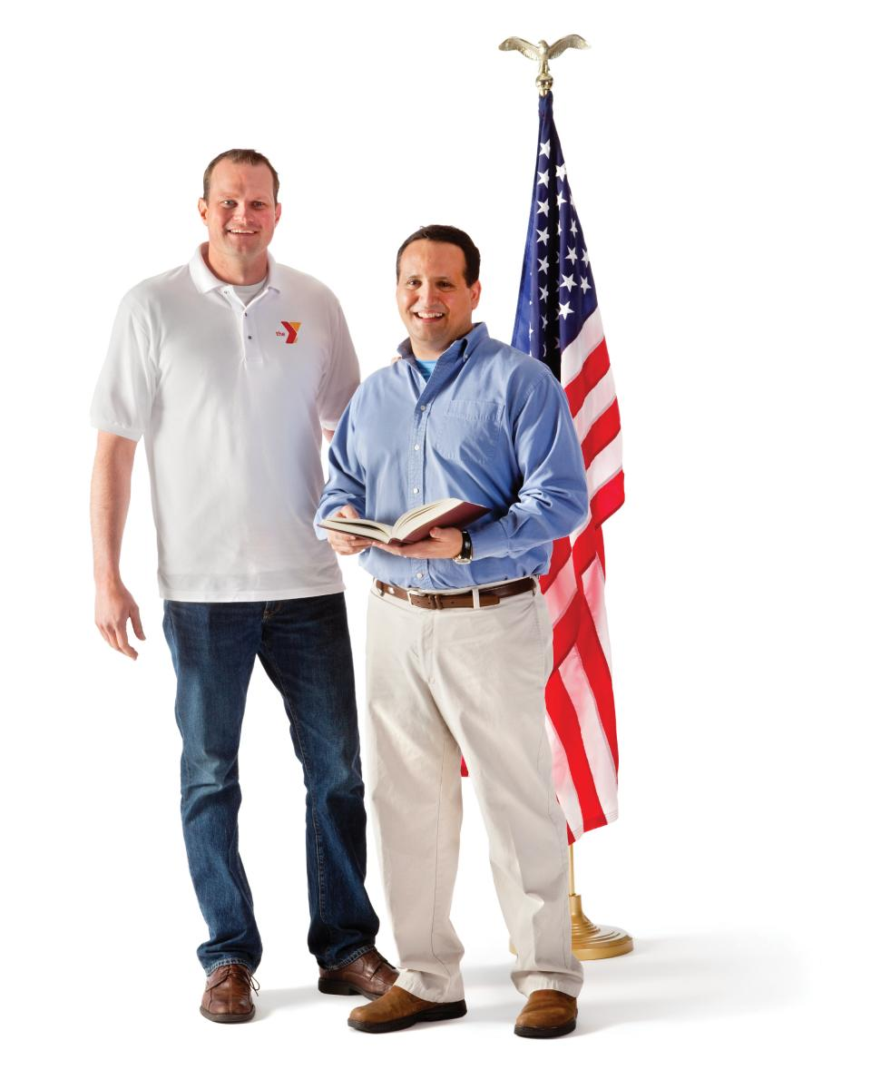 Two men standing in front of American flag.