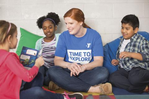 Adult girl listening to children read to her.
